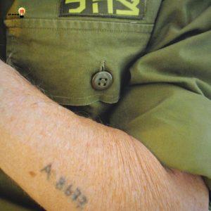 ניצול שואה לבוש במדי צה״ל, עם מס׳ מקועקע על זרועו